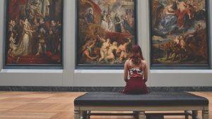 Chica mirando obra de arte en museo